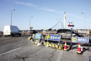 """昨天有市民向本报反映,前日经过富民桥时,发现该桥还是两侧车道均能正常通行,但昨日富民桥却突然""""瘦身""""了,由河西区向河东区方向行驶的车道封闭了,往来该桥的车辆只能从另一半的车道通过。"""