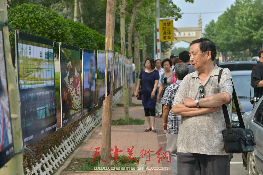 """第四届""""天穆杯""""书画摄影展在北辰区天穆东苑举行,图为天穆村民参观作品。"""