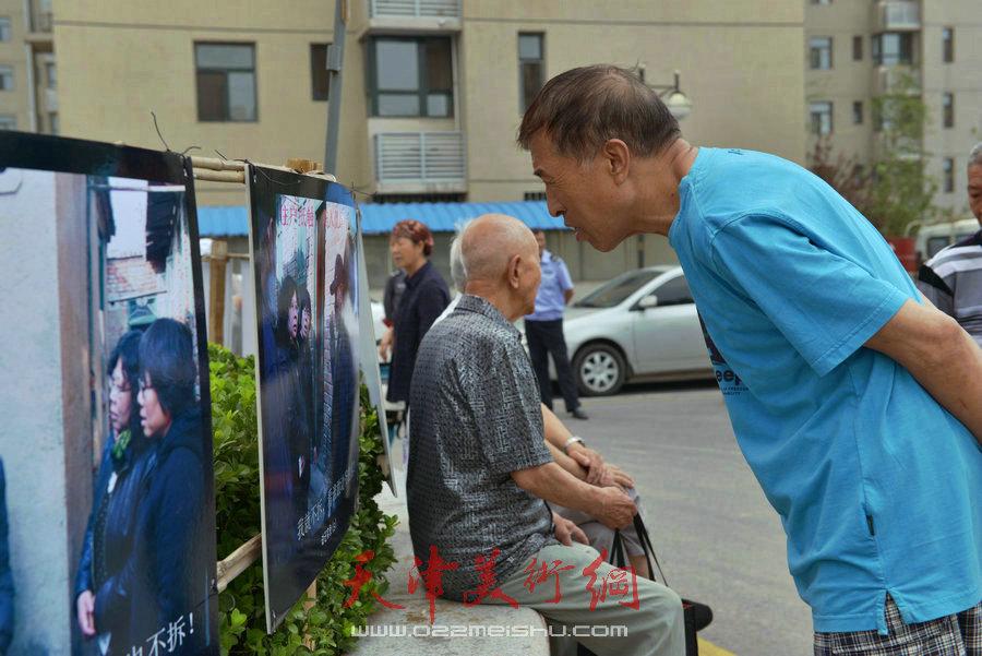 """第四届""""天穆杯""""书画摄影展在北辰区天穆东苑举行,图为观众参观作品。"""