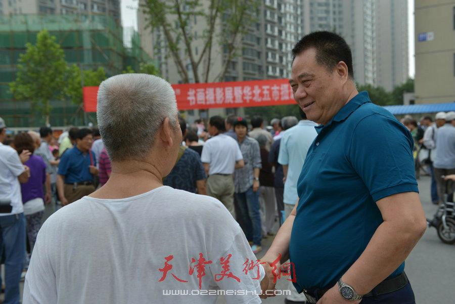 """第四届""""天穆杯""""书画摄影展在北辰区天穆东苑举行,图为天穆村党委书记穆祥友与村民交谈。"""