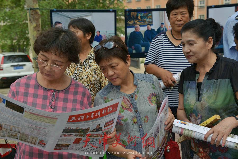 """第四届""""天穆杯""""书画摄影展在北辰区天穆东苑举行,图为观众阅读《天穆书画摄影报》。"""