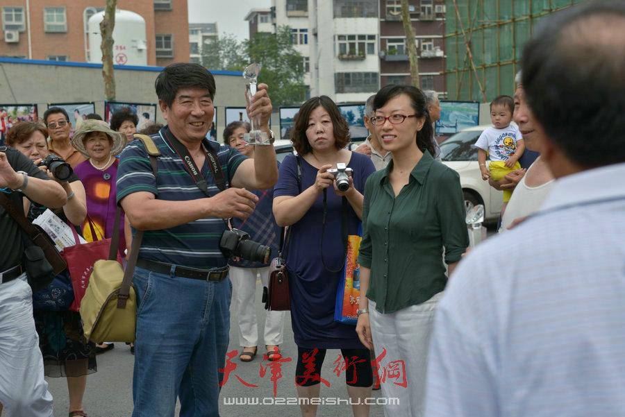 """第四届""""天穆杯""""书画摄影展在北辰区天穆东苑举行,图为获奖者高举奖杯。"""