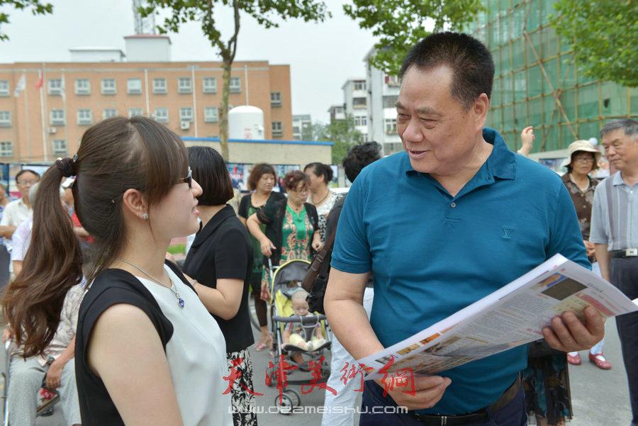 """第四届""""天穆杯""""书画摄影展在北辰区天穆东苑举行,图为穆祥友与观众交谈。"""