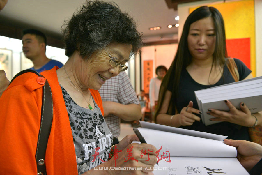 爱新觉罗家族书画展在天津文庙开展,图为毓崧在作品集上签字。