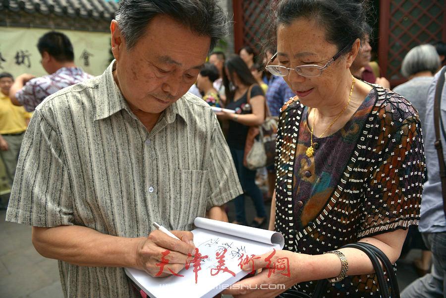 爱新觉罗家族书画展在天津文庙开展,图为赵毅在作品集上签字。