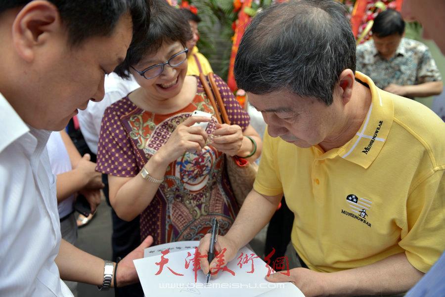 爱新觉罗家族书画展在天津文庙开展,图为毓峋在作品集上签字。