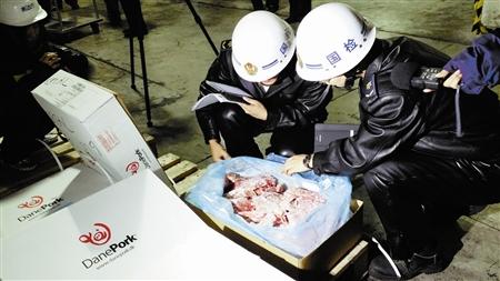 检验检疫人员逐一开箱,对进口冻肉进行感官检查。