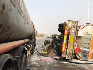 一辆装载有近30吨危险品的罐车撞桥后侧翻,由于罐体顶部的阀门损坏,部分危险品泄漏,多个部门紧急到场处理。