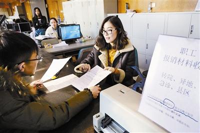 唐山市医保部门工作人员(右)为当地群众办理转诊天津市肿瘤医院相关备案手续。