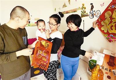 昨天,天津市义工服务队志愿者王芸(右一)给在津治病的山东籍小安然一家送去了年货,表达天津人民的新春祝福。周勤隆摄