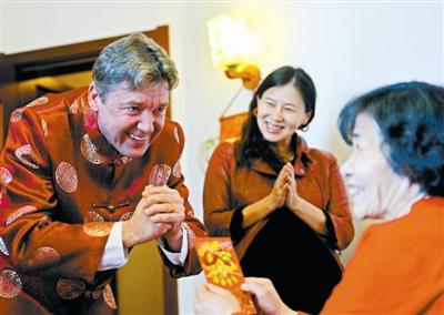 """西蒙用中国传统的作揖礼仪向老人拜年""""讨红包""""。"""